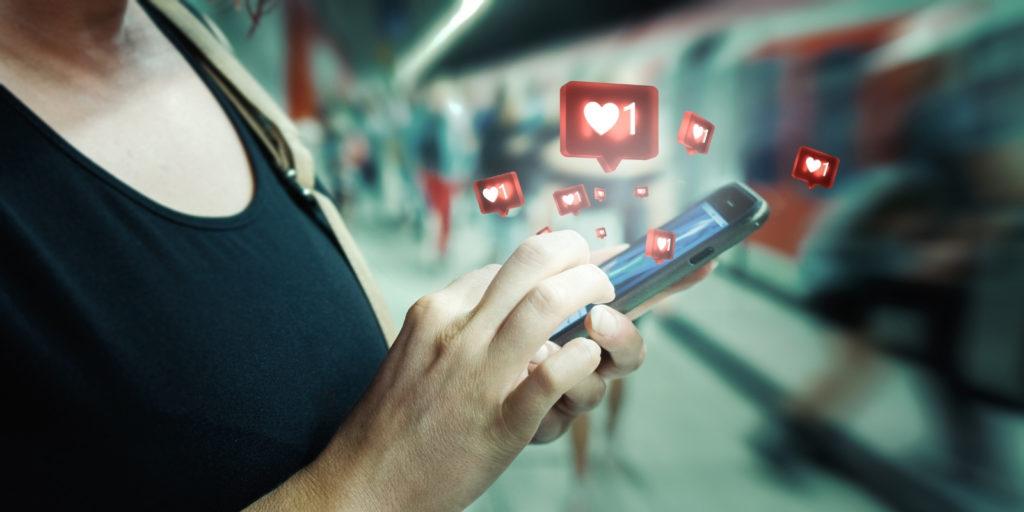 Imagem de uma mão segurando o celular e saindo corações da tela